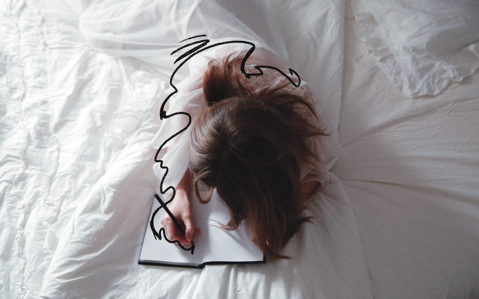 An aerial shot of a woman laying in bed, writing in a journal.