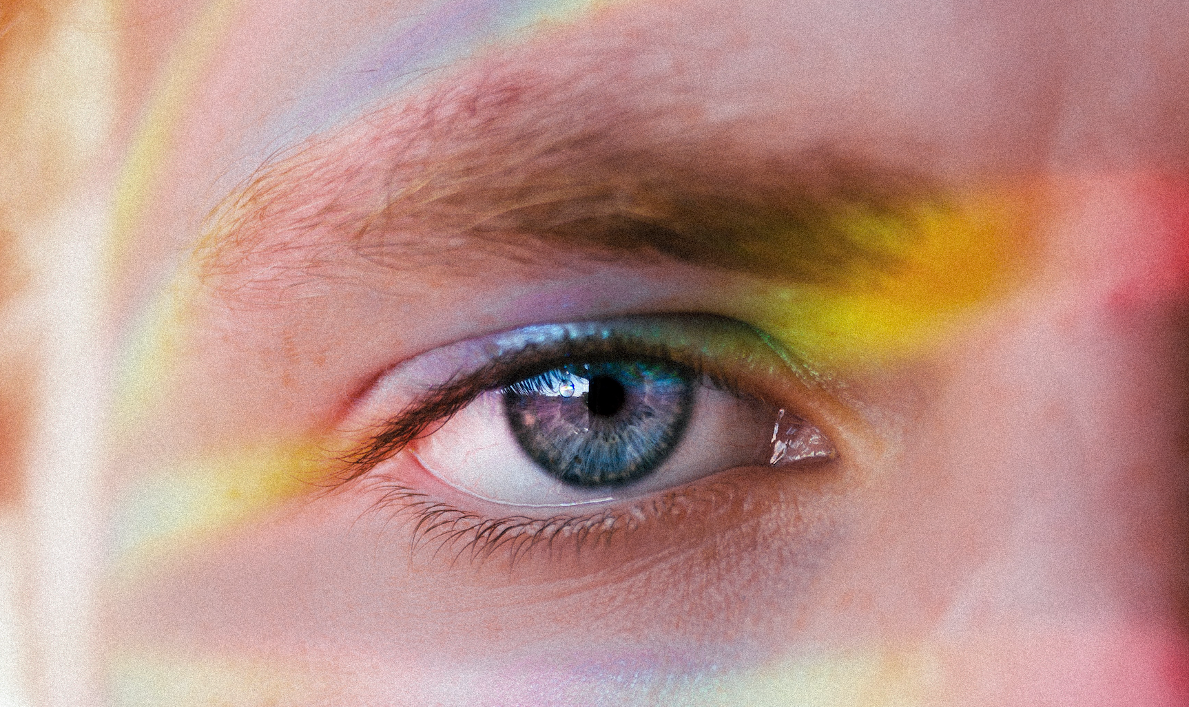 A close up a man's left eye with a rainbow reflecting on his face.