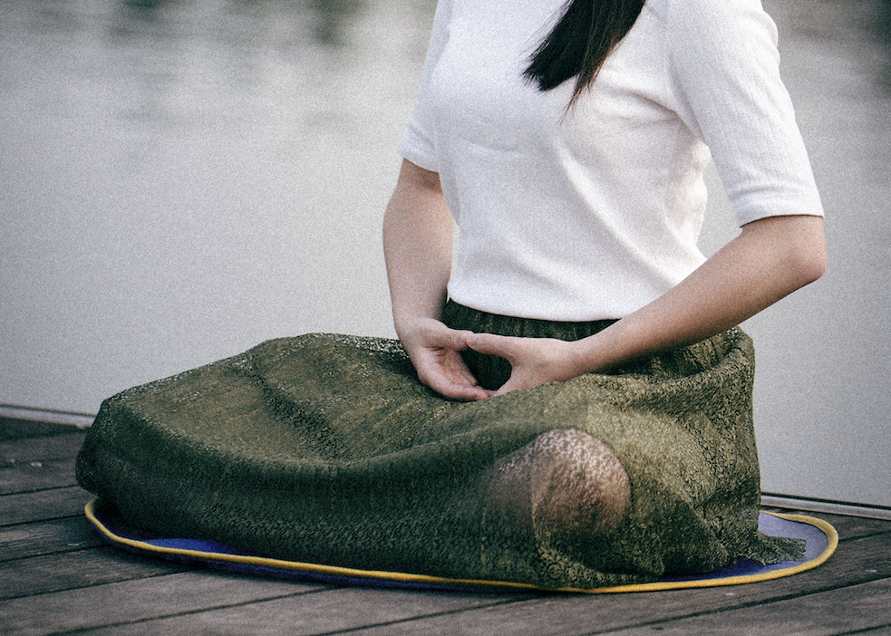 A close up of a woman's body. She sits crossed legged with her arms in her lap on a dock.