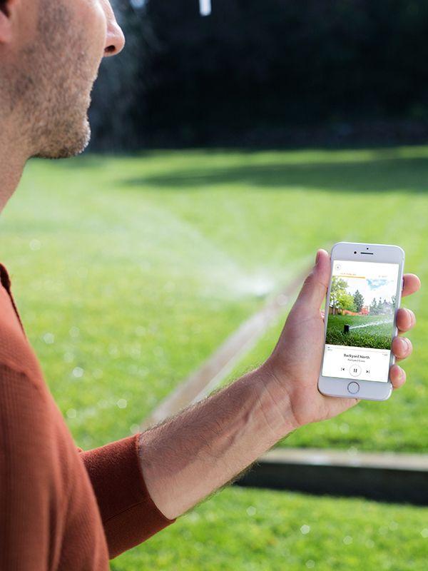 Person using Rachio app in their yard