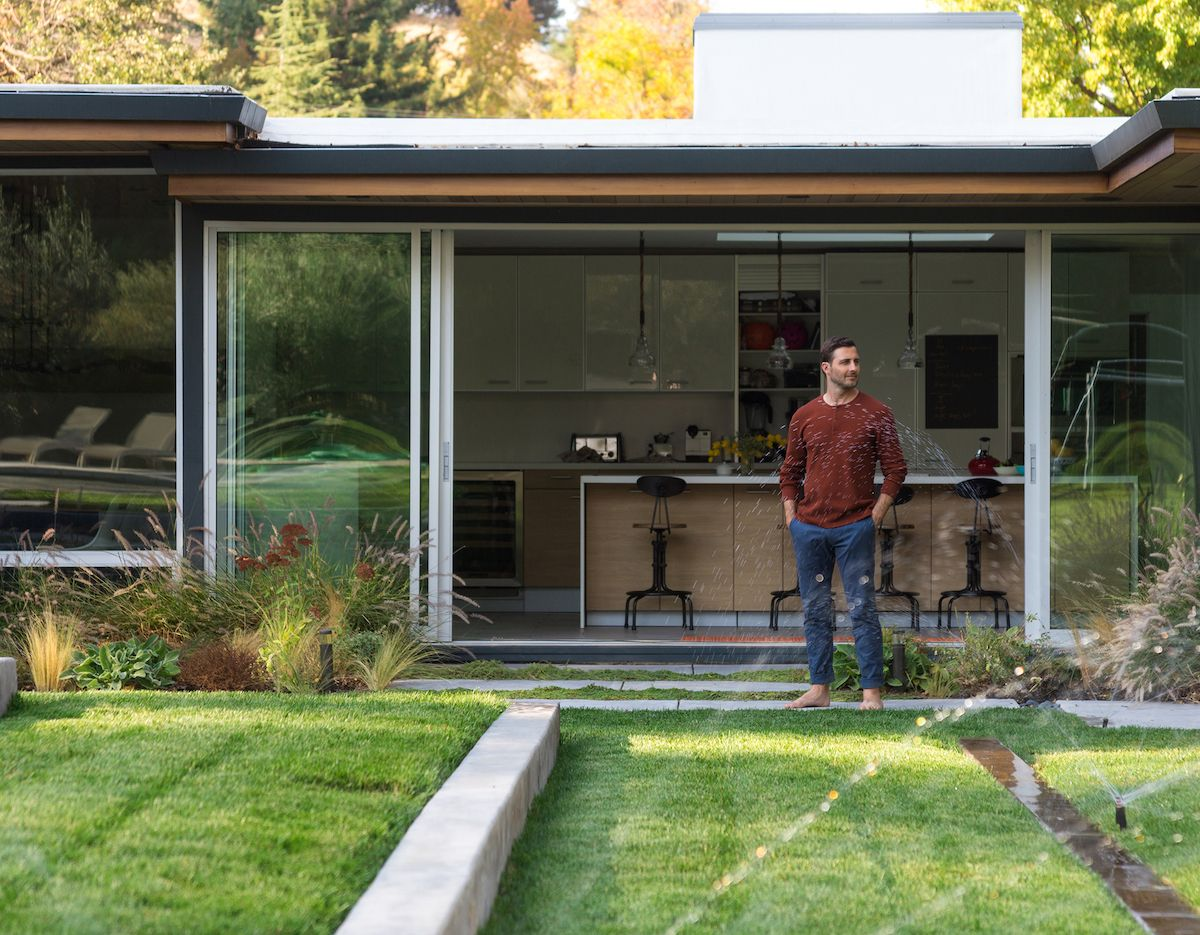 Man standing in yard admiring his working sprinkler system