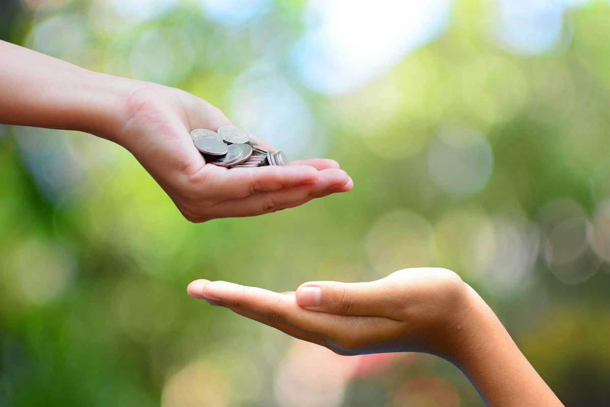 En håndfull mynter holdes over en tom hånd