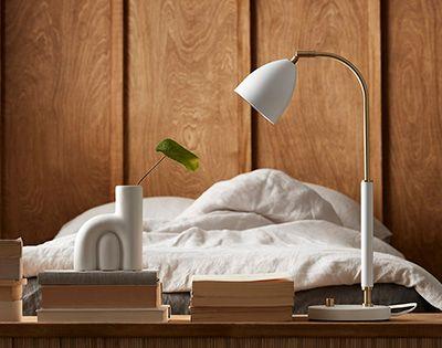 Vit bordslampa framför en säng