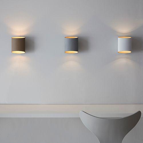 Tre vita vägglampor på en ljus vägg