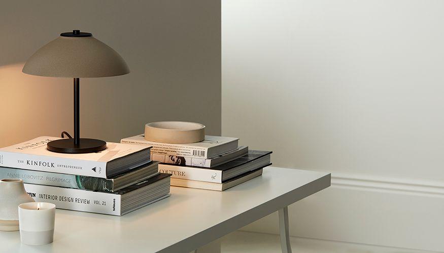 En låg bordslampa på en hög med böcker