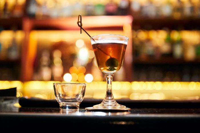 An amber cocktail with an olive on a stick sitting on a bar
