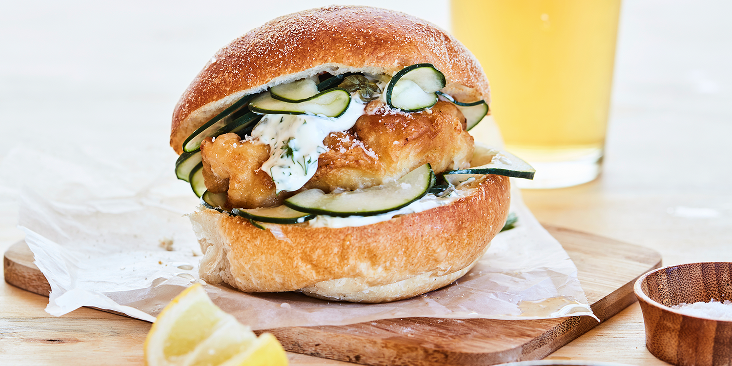 Fish and pickled cucumber on a wooden board