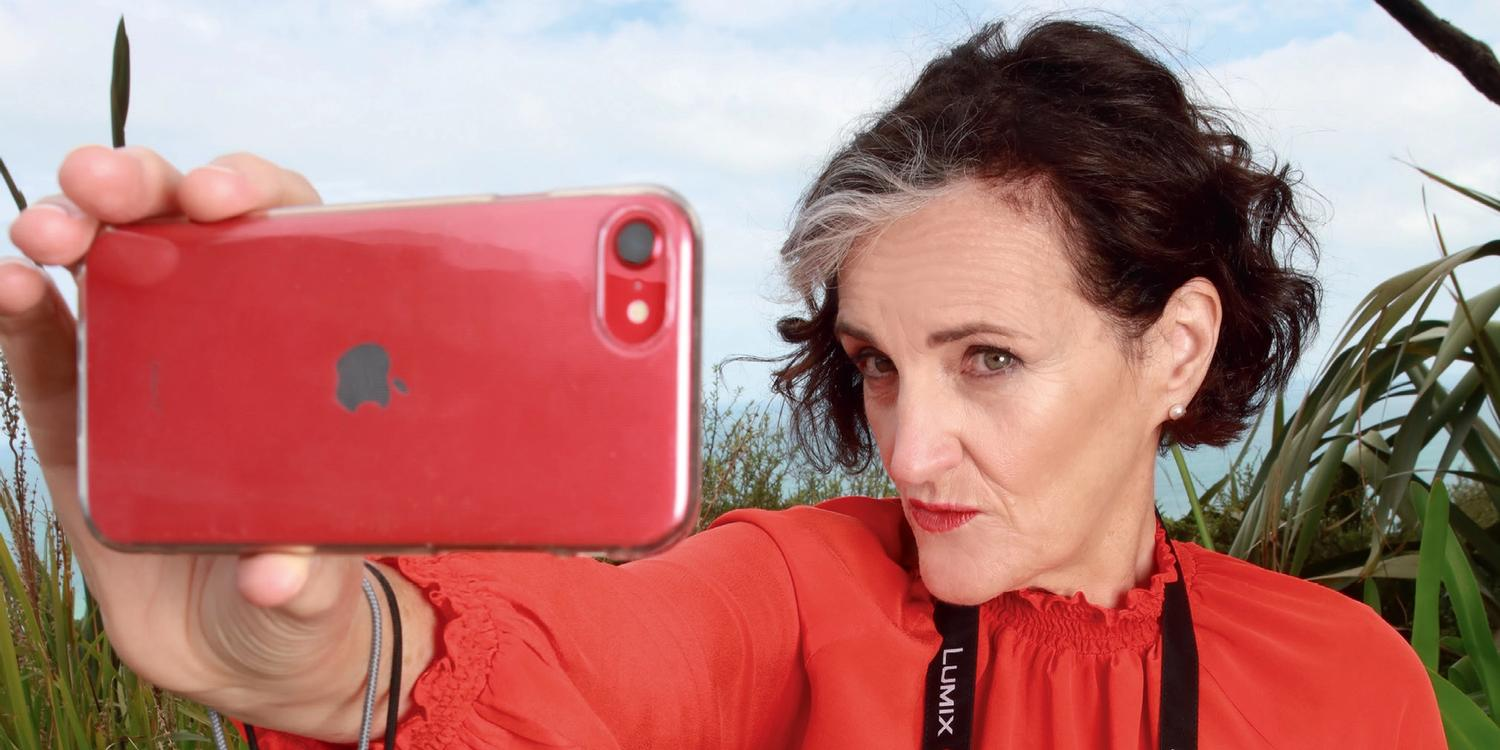 Sarah-Kate Lynch taking selfie while holding multiple cameras