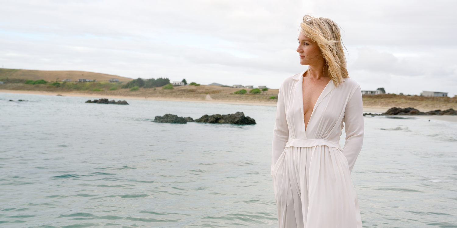 Hayley Holt standing in ocean water wearing a white dress