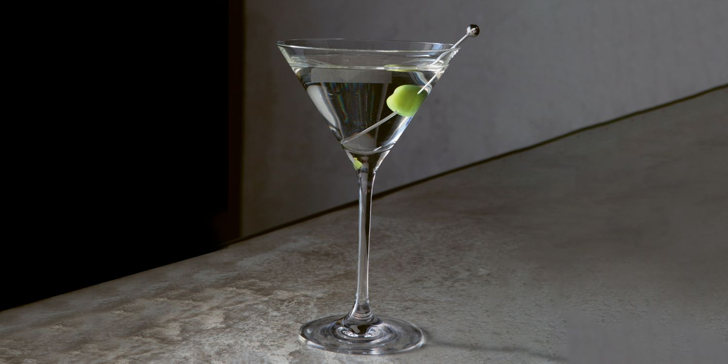 Glass of martini with an olive on a marble background