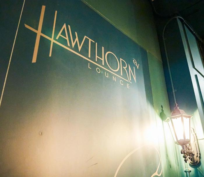 Gold Hawthorn Lounge lettering on dark green wall