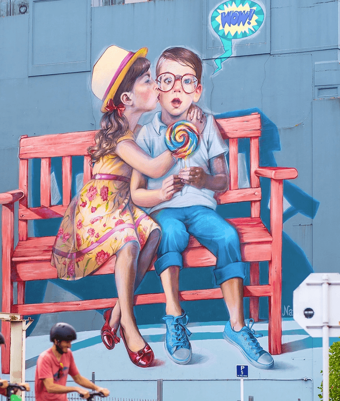 Street art in Dunedin of a little girl and boy eating a lollipop on a red bench