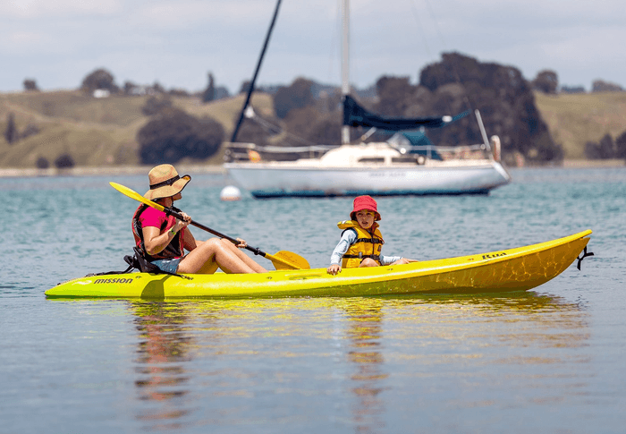 A mother and child in a yellow kayak