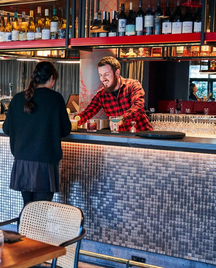 Guy in red and black checked shirt serving cocktails to a woman