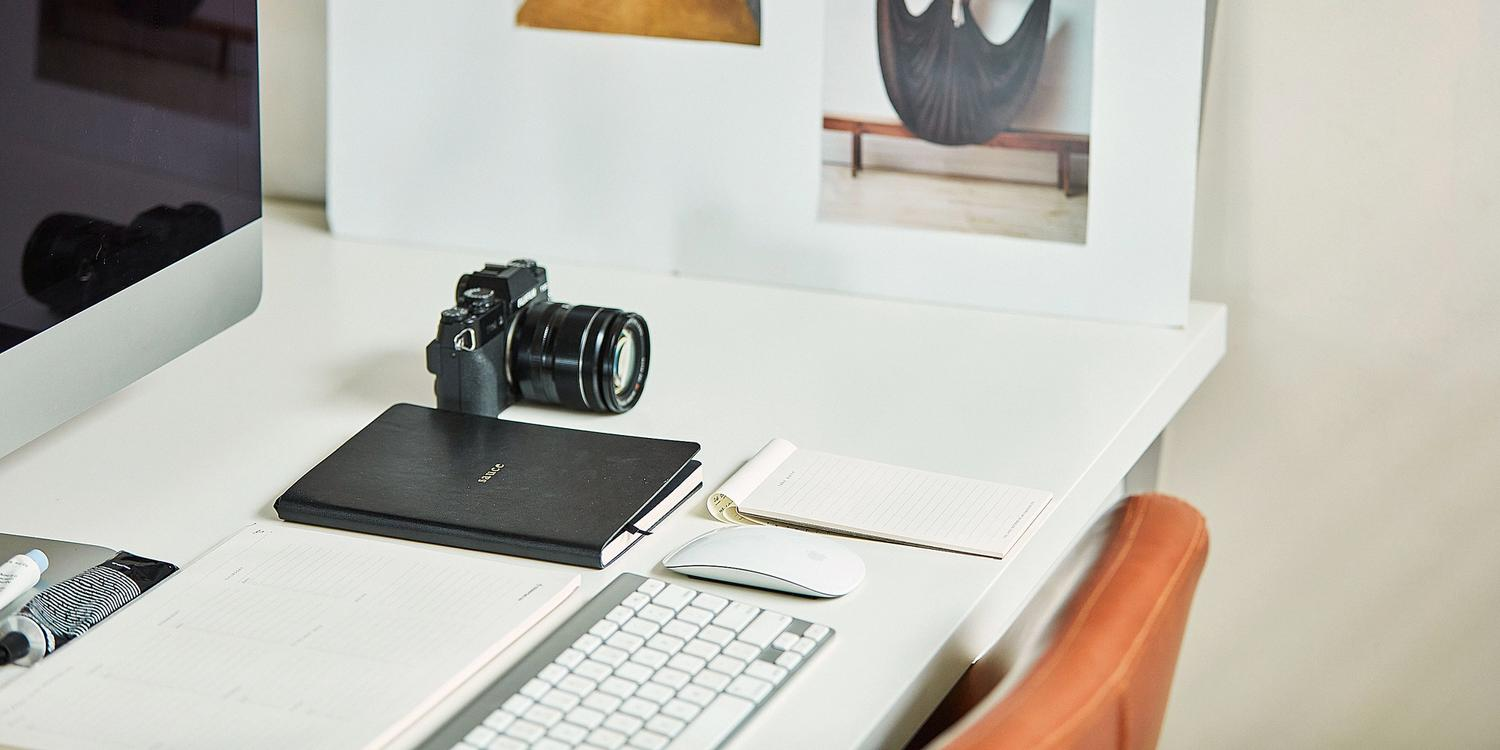 White desk with apple computer, camera and moodboard