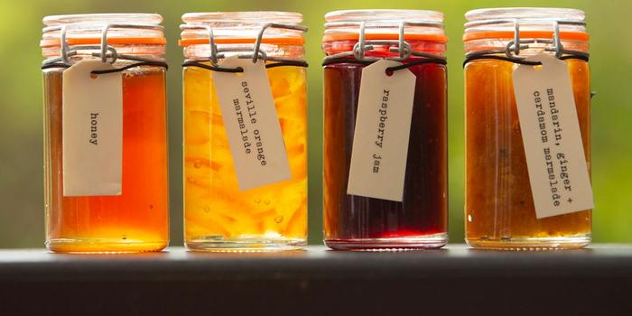 Row of jars filled with homemade marmalade, jam and honey