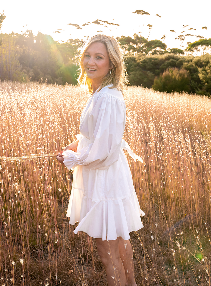 Hayley Holt standing in a wheat field looking at camera