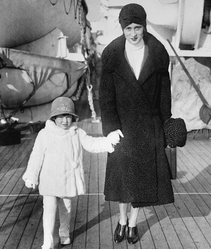 A black and white photo of a young Gloria Vanderbilt with her mother in 1928