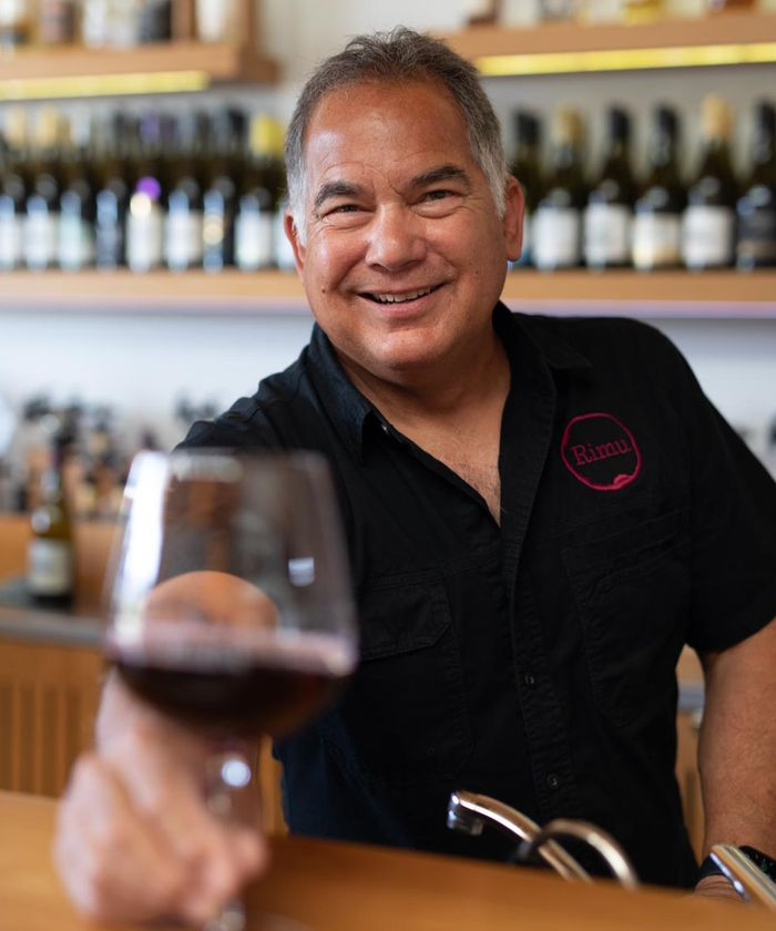 Man serving a glass of red wine at Rimu