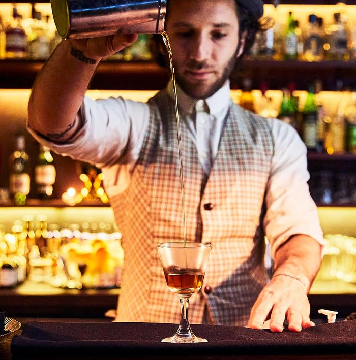 Man in checked waistcoat pouring amber cocktail from a height