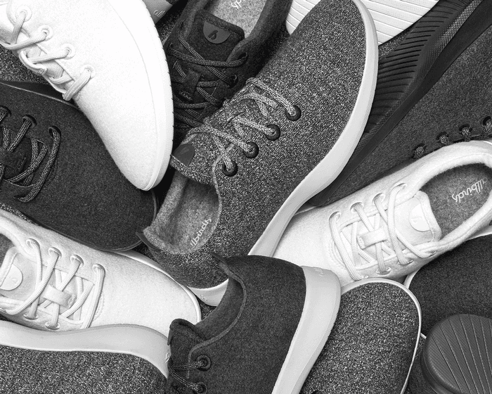 A black and white photo of a pile Allbirds Wool Runners