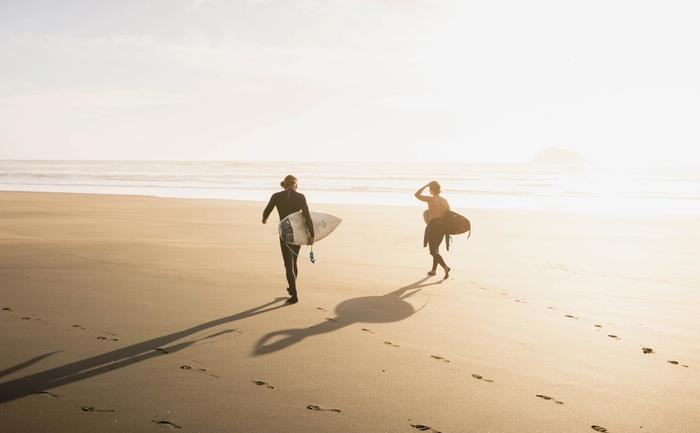 Surfers walking into the sunset at Muriwai beach