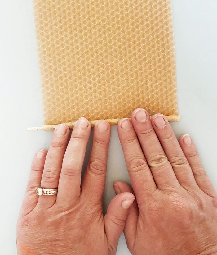 Two hands rolling beeswax