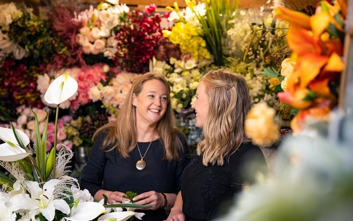 Heather Boswell-Nguyen and Abbey Lang surrounded by flowers