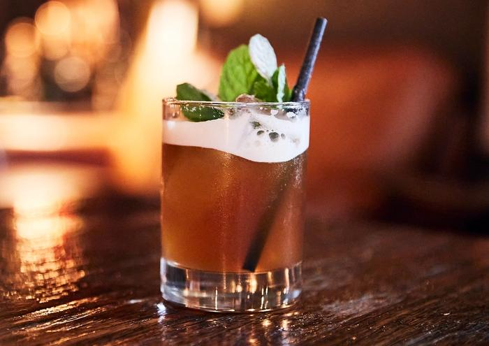 Amber frothy drink with mint leaves in short glass