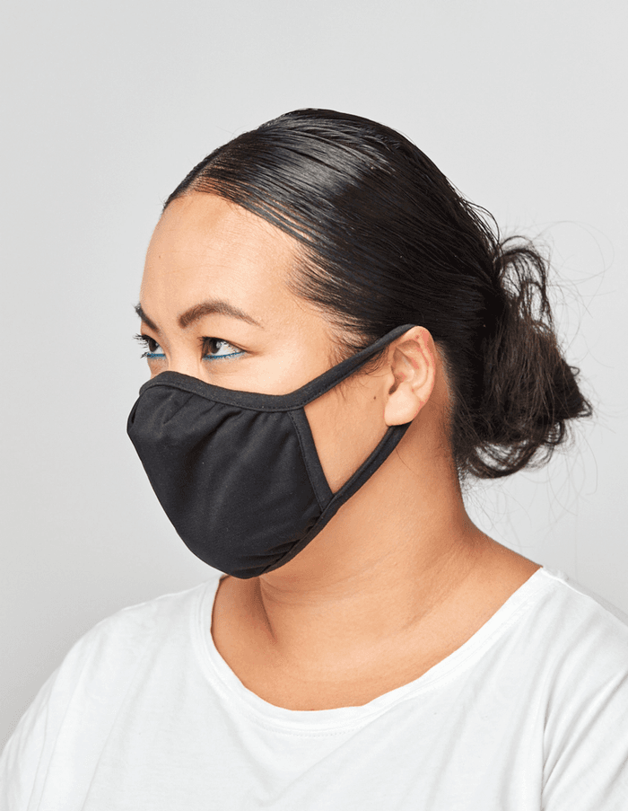 Model with hair in a bun and wearing black face mask