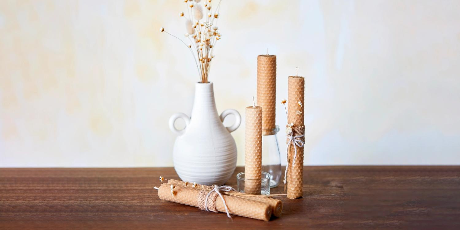 A white vase surrounded by honey candles