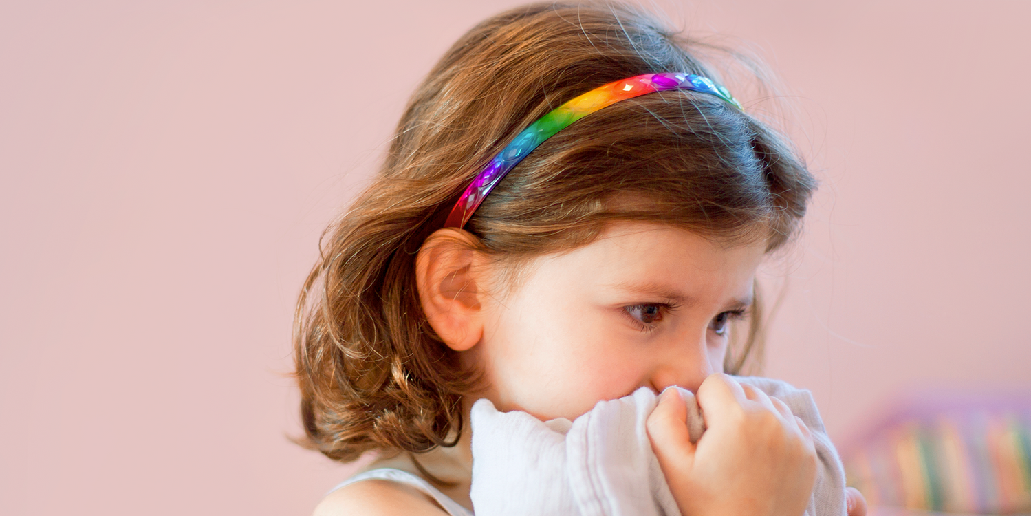 A little girl holding a blanket to her face anxiously