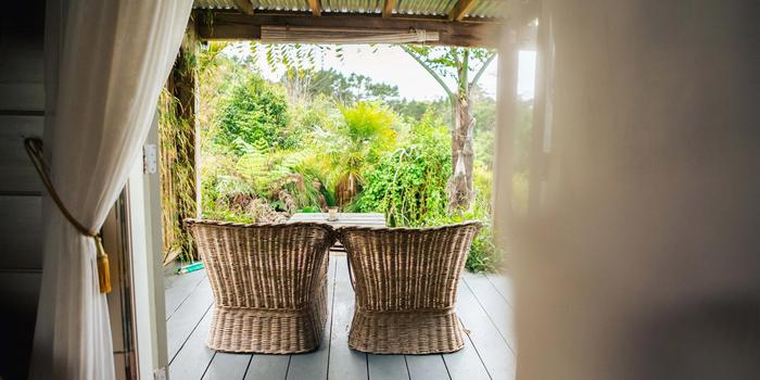 Deck with two cane chairs at Muriwai