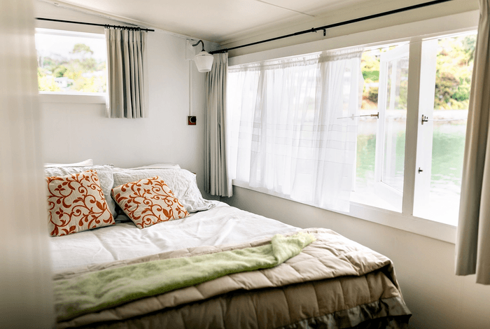 Double bed with red colourful cushions and windows opening to the sea