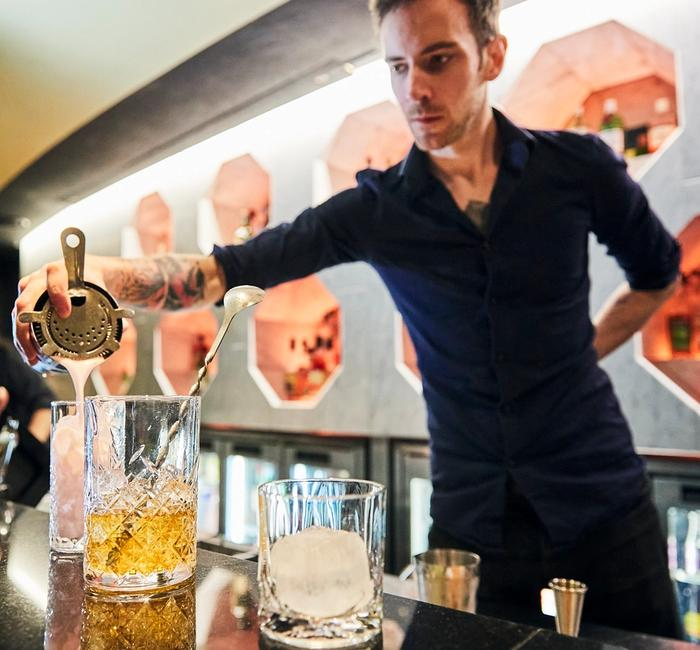 Bartender in black pouring cocktail through a strainer