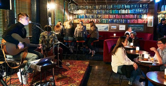 Man singing and playing guitar to full bar lined with books
