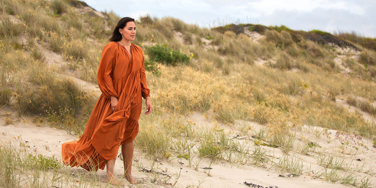 Makaia Carr standing on beach wearing coral dress