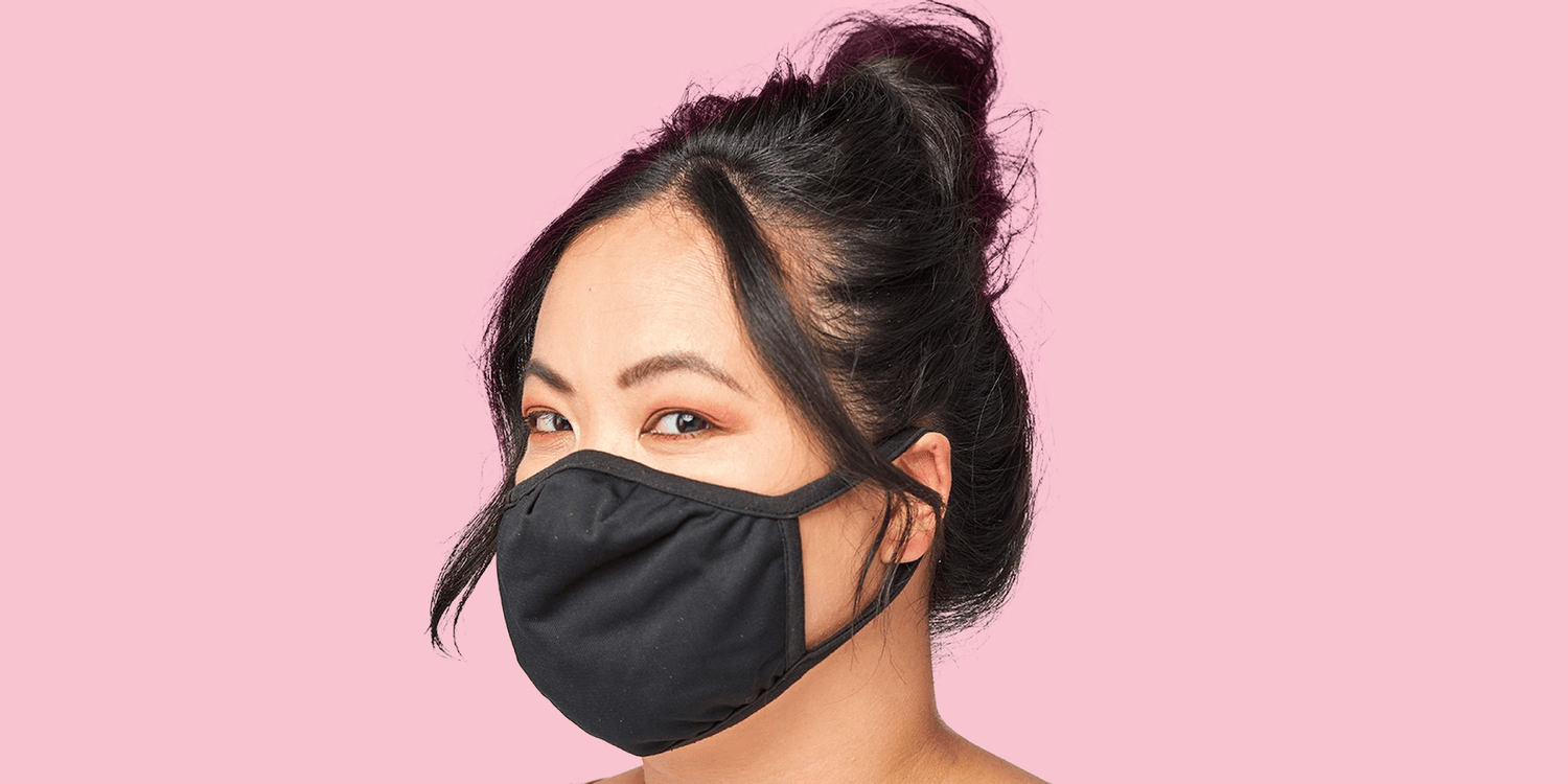 Model wearing black face mask while standing against pink background