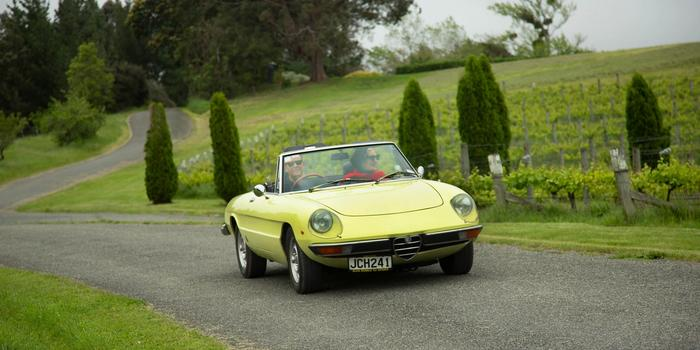 1975 convertible Alfa Romeo Spider driving through green hills