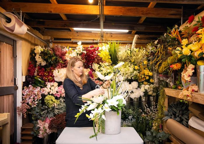 Heather from Curated Botanics arranging a floral arrangement