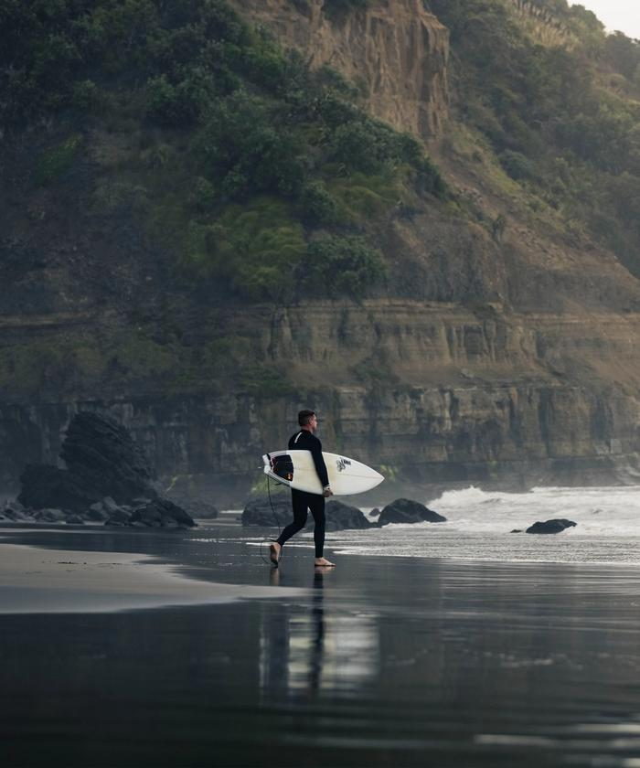 Surfer walking into the Muriwai surf