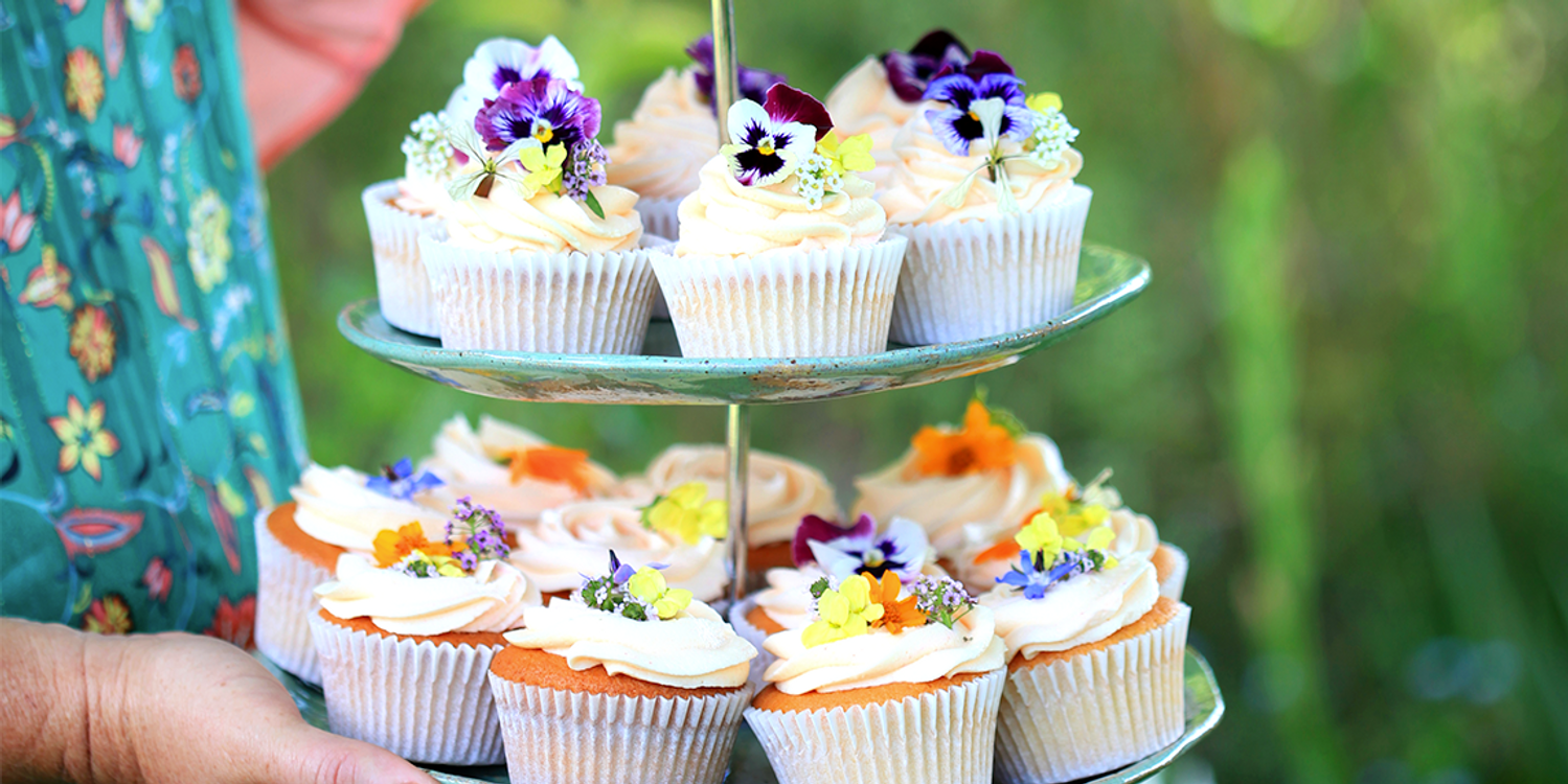 A woman's hand holding a plate of cupcakes with icing covered in petals
