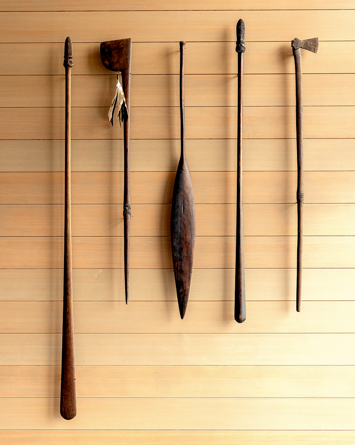 A collection of Māori artifacts hanging on a wooden wall at The Landing