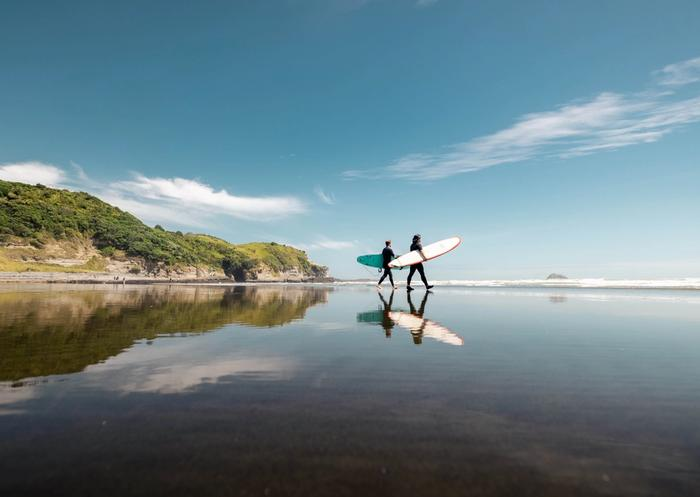 Surfers walking to the sea at Muriwai beach