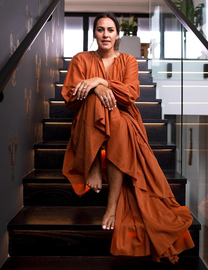 Makaia Carr in rust coloured dress sitting on staircase