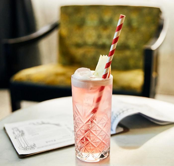 Pale pink tall cocktail with red and white striped straw