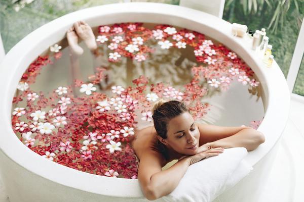 Woman relaxing in a sea salt soak detox bath using the Staycation Set by the Feelist