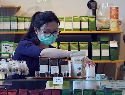 A lady buying tea while wearing a mask