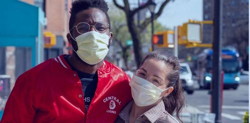 Two people on the street wearing masks
