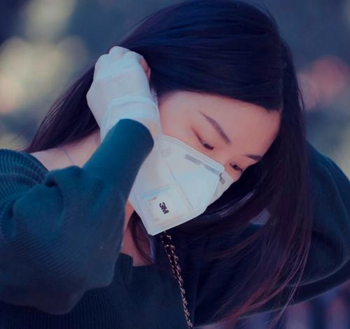 woman on public transportation with a mobile phone wearing a mask